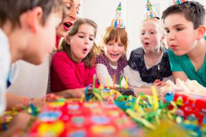 Child on birthday party blowing candles on cake